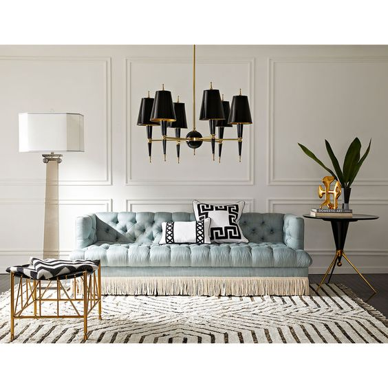 living room, dark wooden floor, white rug, soft blue tufted sofa, white wall, black covered chandelier, black white stool with golden legs, black side table, white floor lamp