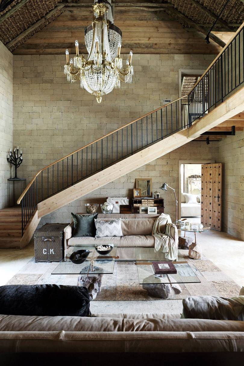living room, light wooden floor, brown sofa, rug, glass top coffee table, stairs, chandelier, conblock