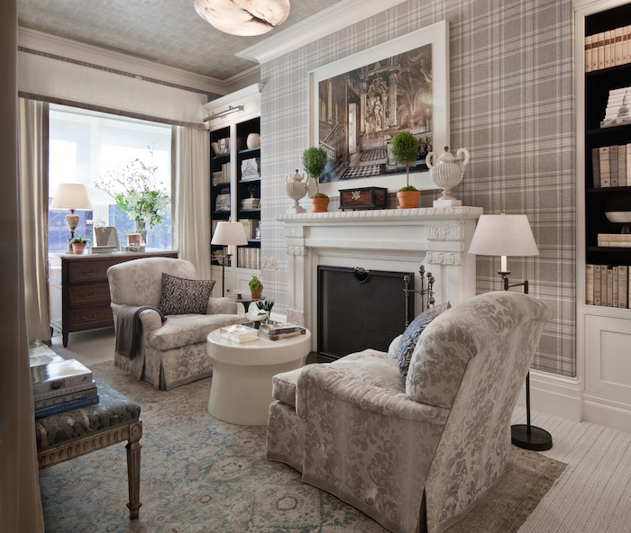 living room, patterned neutral rug, plaid wallpaper, white fireplace, patterned chairs, white round coffee table, wooden cabinet, built in shelves, white floor lamp