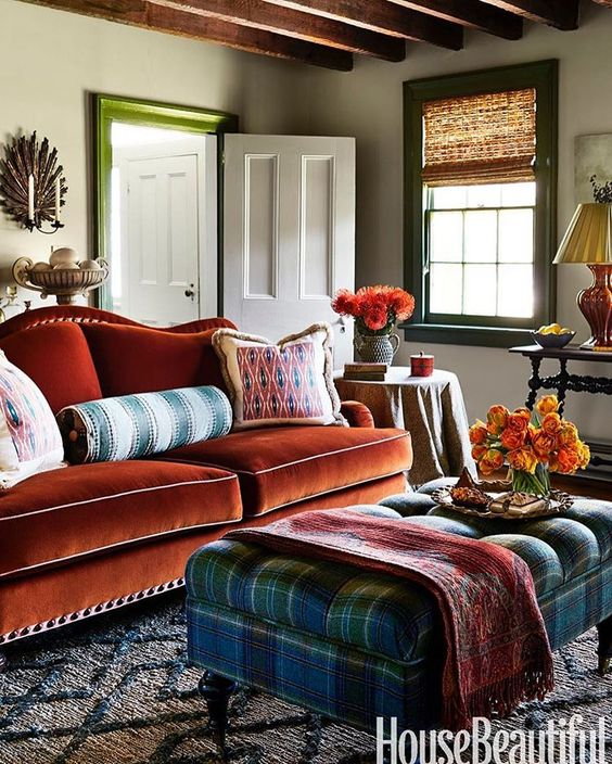 living room, patterned rug, tufted blue green plaid ottoman, orange velvet sofa, white wall, green window frame, white door, side table