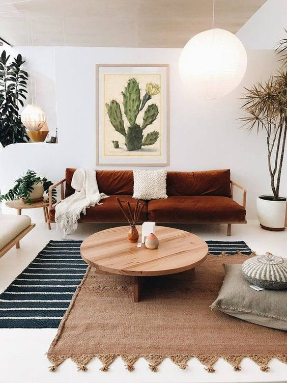 living room, white floor, striped rug, brown rug, wooden coffee table, white wall, white pendant, wooden bench brown grey cushion, white pot, wooden side table