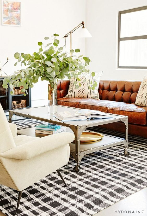living room, white floor, white wall, coffee table, white chair, brown leather sofa, white floor lamp, black white plaid rug