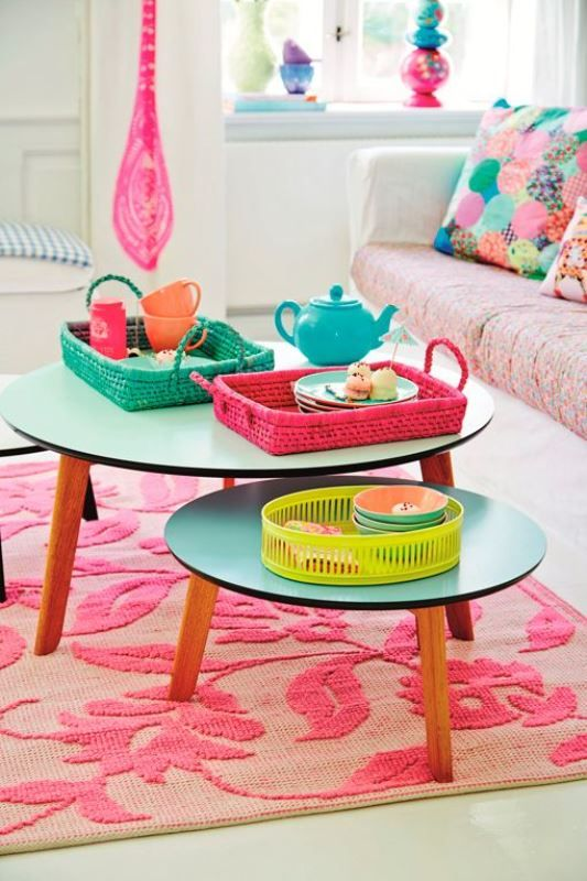 living room, white floor, white wall, pink sofa, turquoise round nesting coffee table, pink patterned rug