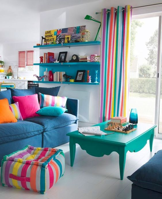 living room, white floor, white wall, turquoise floating shelves, turquoise coffee table, blue sofa, colorful ottoman, colorful curtain, white wall