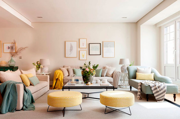 living room, white rug, white sofa, green lounge chair, square coffee table, off white wall, pale yellow ottoman, side table, white covred table lamp