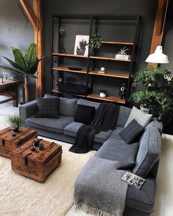 living room, white wooden floor, dark wall, black shelves, wooden posts, grey sofa, wooden chest coffee table, white rug, white pendant