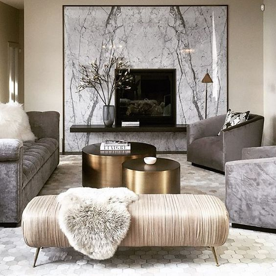 living room, whtie hexagonal floor tiles, beige wall, marble wall decoration, floating black shelves with TV, grey sofa, grey chairs, white bench, gold round coffee table