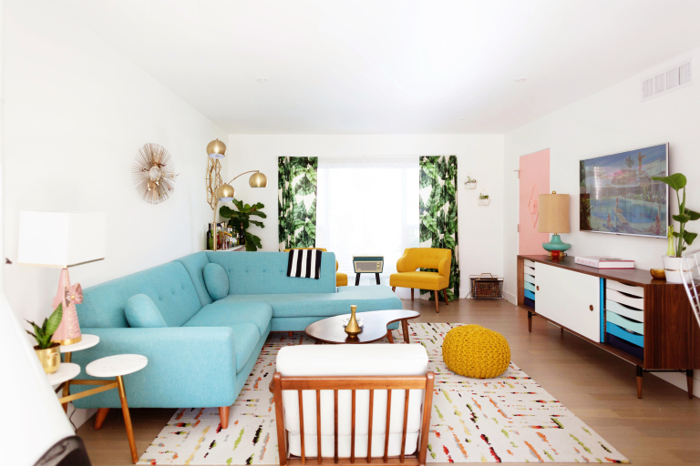 living room, wooden floor, curvy coffee table, yellow woven ottoman, yellow velvet chair, blue sofa, white chair, white rug, white wall