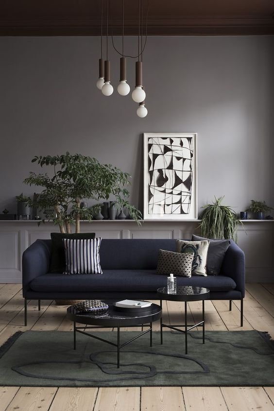 living room, wooden floor, dark green rug, dark blue sofa, grey wall, wainscoting, white pendant, black round coffee tables