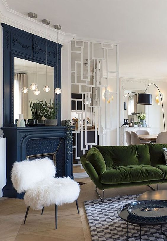 living room, wooden floor, plaid rug, tray tables, white fur chair, white wall, blue fireplace, blue framed mirror, dark green sofa