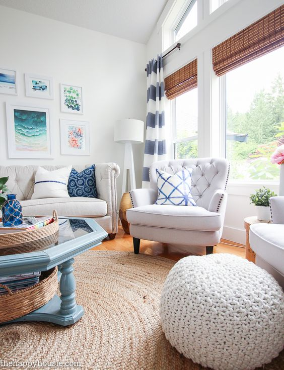 living room, wooden floor, rattan rug, white wall, white sofa, white chair, white woven ottoman, blue glass coffee table