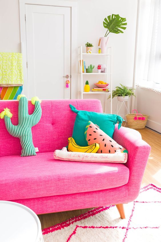 living room, wooden floor, shocking pink sofa, white wall, pink white patterned rug