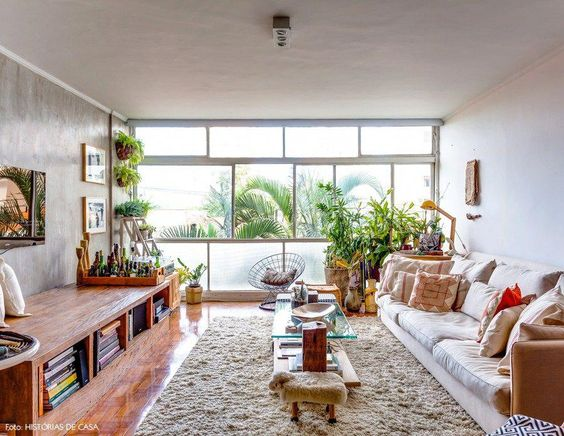 living room, wooden floor, white rug, woden coffee table with glass top, white sofa, wooden cabinet with shelves under, shaded and clear glass window