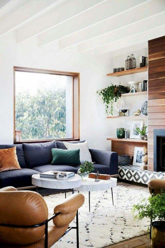 living room, wooden floor, white wall, white ceiling, white rug, white marble nesting table, dark grey soaf, brown leather chair, fireplace with wooden accent wall