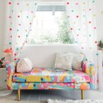 Living Room, Wooden Floor, White Wall, White Curtain With Colorful Dots, White Rug, Colorful Patterned Sofa, White Pillows