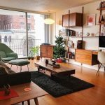 Living Room, Wooden Floor, Wooden Cabinet, Wooden Floating Cabinet, Wooden Floating Shelves, Black Rug, Wooden Coffee Table, Wooden Side Table, Sofa, Green Lounge Chair