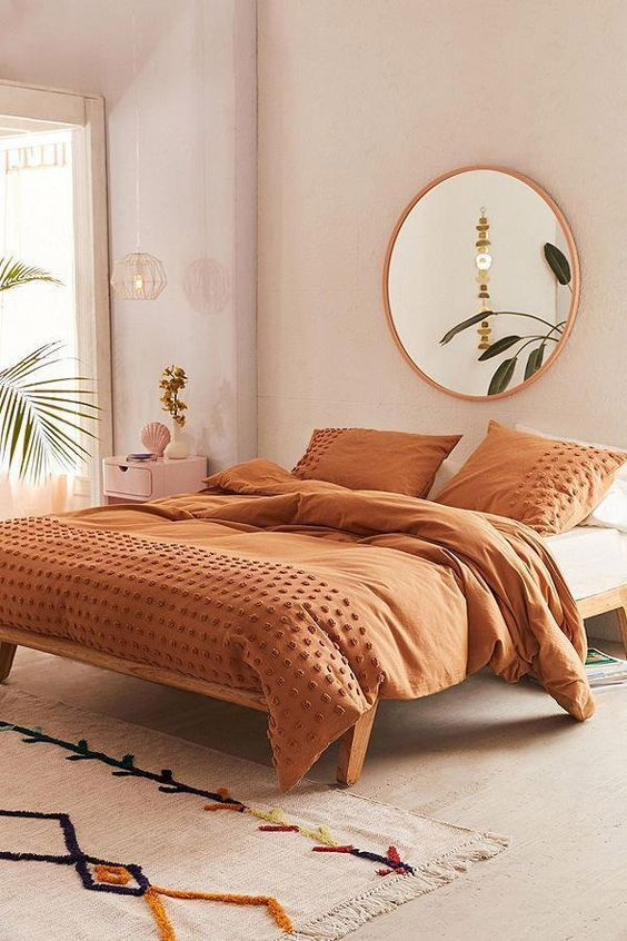 master bedroom, beige seamless floor and wall, wooden bed platform, beige rug, tan blanket, round mirror