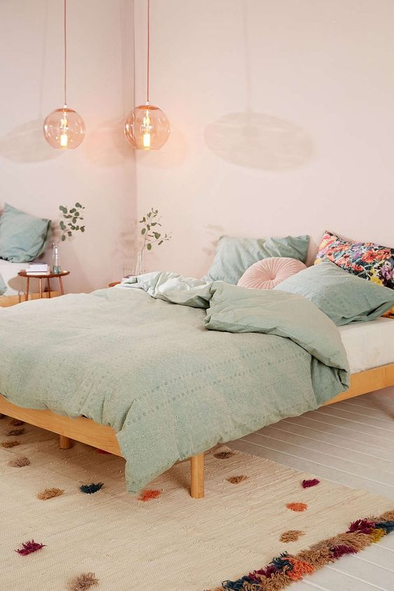 master bedroom, white wooden floor, beige rug, wooden bed platform, green blanket, white wall, wide table, glass bulb pendant