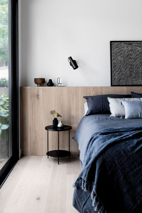 master bedroom, wooden floor, wooden wainscoting, white wall, glass window, black side table, blue bedding