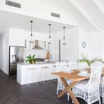 Open Kitchen, Dark Herringbone Floor Tiles, White Walls, White Vaulted Ceiling, White Kitchen Cabinet And Top, Wooden Stools, Wooden Table, White Chairs, Glass Pendant