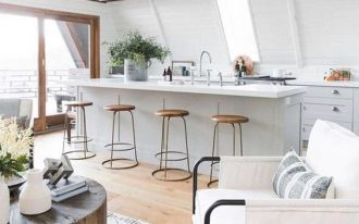 open kitchen, wooden floor, white sloping wall, white ceiling, wooden vaulted ceiling, round wooden table, white chair, wooden stools