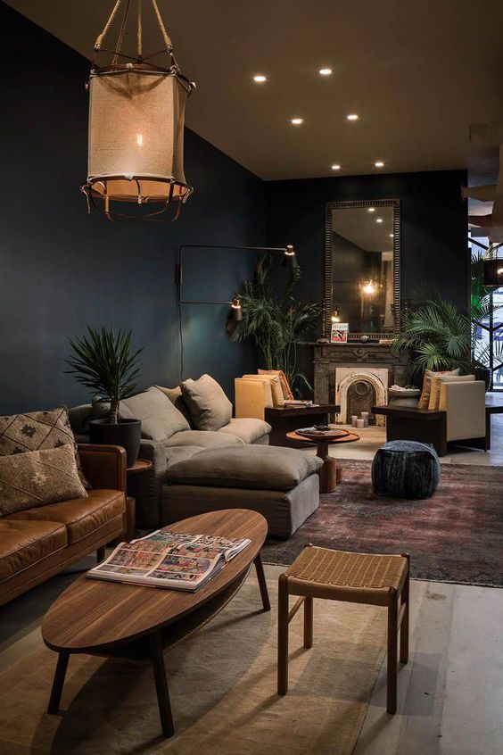 open living room, white rug, brown floor, dark green wall, beige chairs, grey sofa, leater sofa, wooden coffee table, rattan stools, round wooden coffee table, dark blue stool