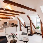 Open Room Under The Attic, Small Kitchen, White Dining Set, Living Room, White Chair, Black Chair, White Floor, Firepace, Wooden Beams