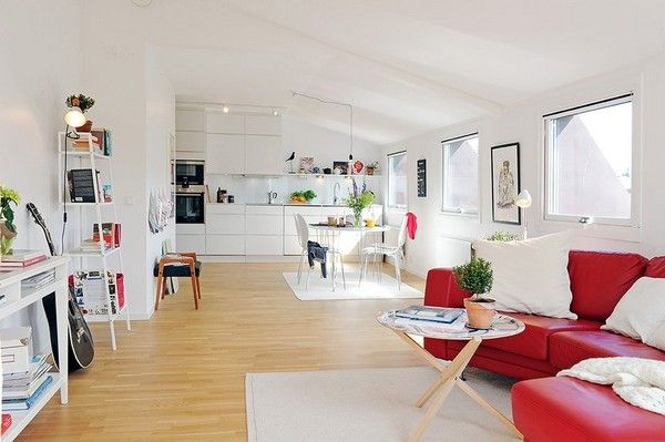open room under the ceiling, wooden floor, white wall, whtie shelves, white rug, white dining set, white kitchen cabinet, red sofa, wooden round coffee table, white table