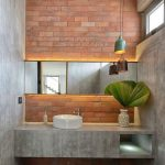 Orange Brick Horizontal Wall Tiles, Long Mirror, Grey Cemented Wall And Floating Vanity, White Round Sink, Patterned Floor