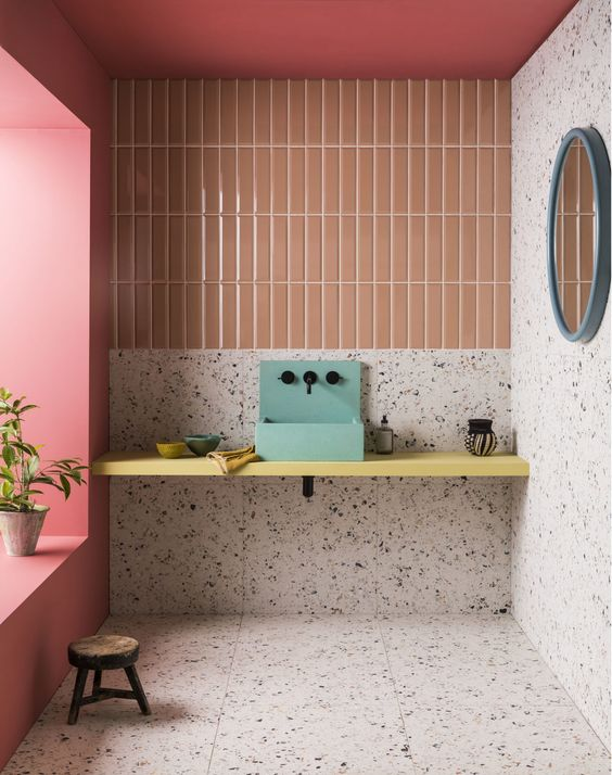 orange vertical lines, terazzo wall, terazzo floor, yellow floating vanity, green sink, blue round mirror, pink accent wall