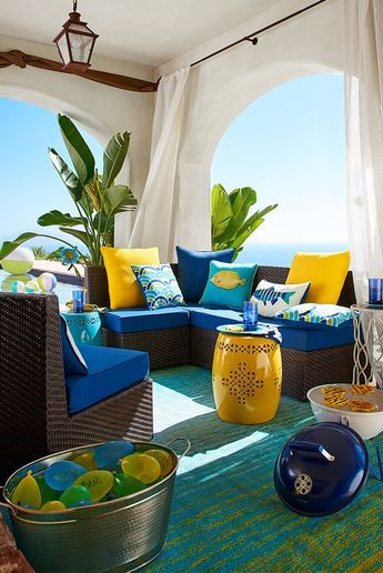 patio, green blue rug, dark brown rattan sofa, dark blue cushion, blue yellow pillows, pendant, yellow pillo