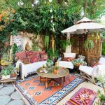 Patio, Round Stone, Colorful Patterned Rug, White Blanket Seating, Round Coffee Table