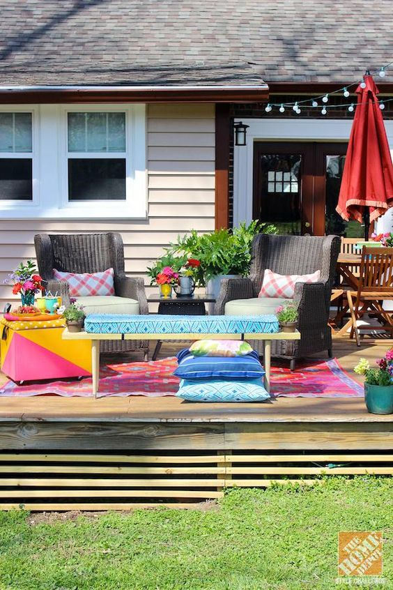 patio, wooden floor, wooden coffee table with blue cushion, dark rattan chair, pink yellow side table,