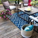 Patio, Wooden Floor, Wooden Rail, Wooden Table, Rattan Chairs, Rattan Side Table, Rattan Basket, Blue Patterned Rug