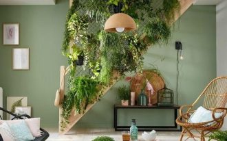 plants on the stair side, wooden floor, rattan rug, wooden table, rattan chairs, green wall, wooden pendant