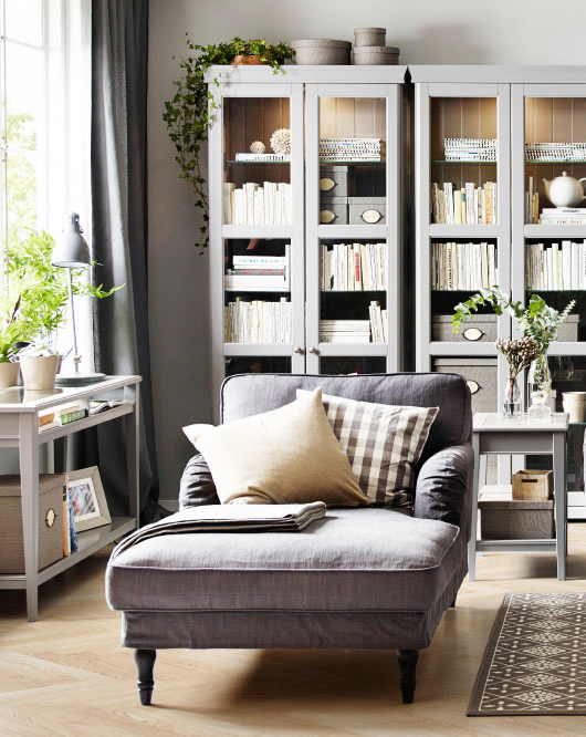 purple lounge chair, wooden floor, white wall, grey book shelves, grey glass table, grey curtain, patterned rug, grey side table