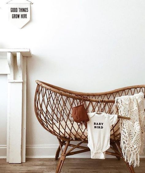 rattan baby crib, white cushion, wooden floor, white wall