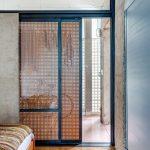 Rattan Doors, Grey Wall, Blue Cabinet, Wooden Herringbone Floor, Colorful Striped Rug, Wooden Bed Platform