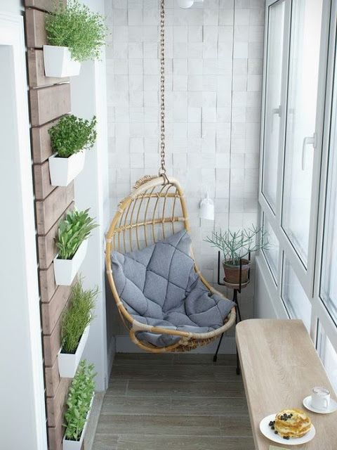 rattan swing with soft blue cushion in the balcony, wooden floor, wooden wall board with plants, floating wooden table