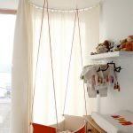 Red Baby Box Hung From The Ceiling, Round Area With Curtain, White Wall, White Floating Shelves, White Wall, Wooden Cabinet