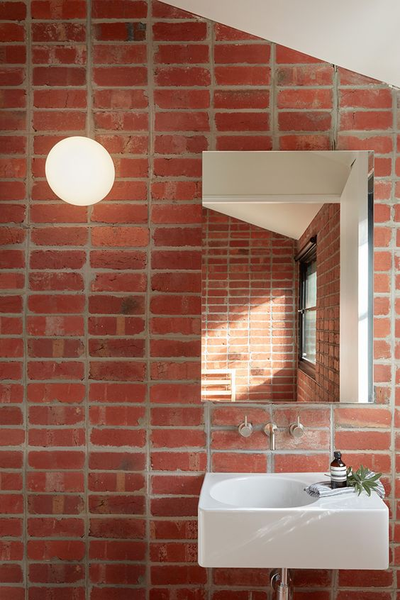 red open brick wall, white square sink, mirror, white sloping ceiling