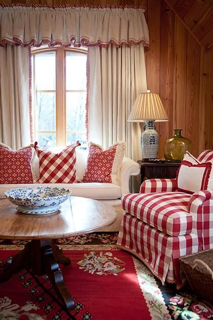 red white plaid chair, red patterned rug, round wooden table, white sofa, wooden wall, white curtain, dark brown side table