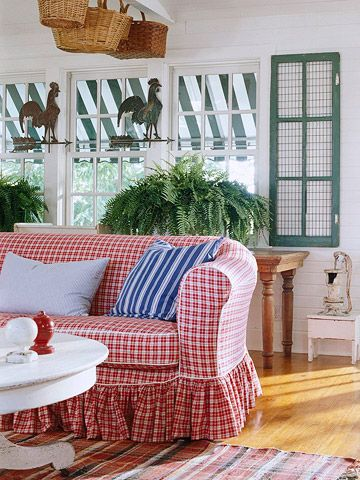 red white plaid sofa, wooden floor, white wall, rattan baskets on the ceiling, white round table