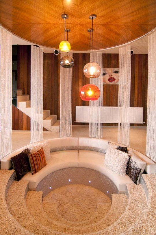 round sunken living room, white sofa, half rug part, white floor, white curtain
