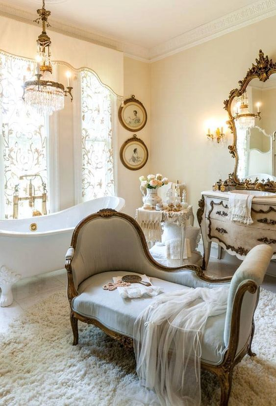 shabby bathroom, white rug, white bench, white wall, white tub, crystal chandelier, beige cabinet, mirror with detailed frame