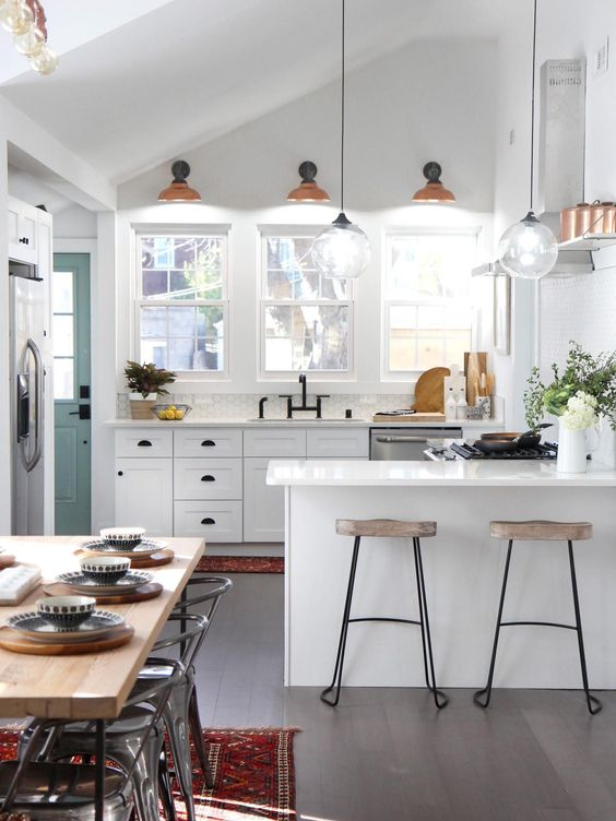small kitchen, wooden floor, white kitchen cabinet, orange sconce, glass bulb pendants, white island, stool, wooden table, industrial chairs, red rug