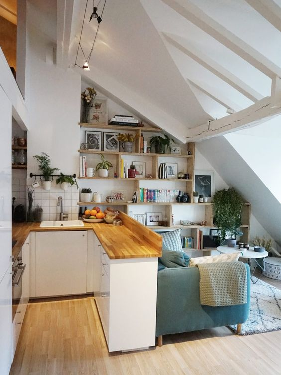 small kitchen, wooden floor, white wall, white cabinet, wooden top, blue sofa, white rug, wooden shelves, white coffee table