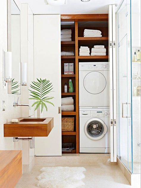 small laundry room with built in cupboard, white door, shelves, marbled floor, brown floating sink, white pendants,