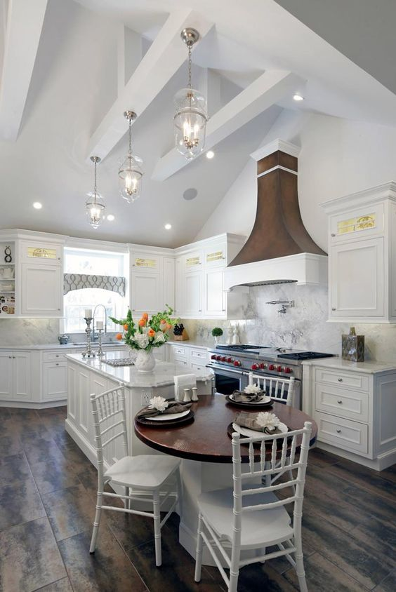 small open kitchen with vaulted ceiling, white cabinet, small round table, white chairs, pendant, wooden hood