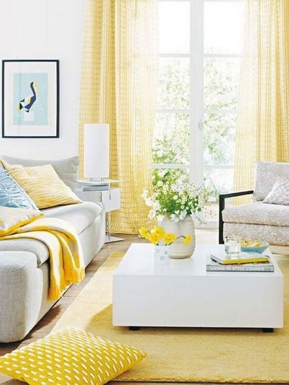 soft yellow living room, yellow rug, white coffee table, soft yellow cutain. yellow blanket pillows, white chair, white side table, white floor lamp